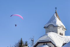 Paragliding. A man having fun paragliding The background is a wonderful blu clear sky and a little moon In the foreground a church's detail stock photo