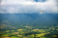 Paragliding in mountains above fields and villages - view from air Stock Images