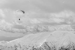Paragliding in mountains in spring time. Blank space for a text. Black and white picture. Men in left upper corner. Royalty Free Stock Photos