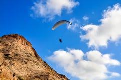 Paragliding nära klipporna Arkivbild