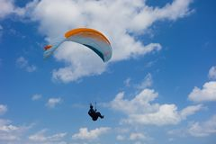 Paragliding at Okinawa. With clear blue sky, expert playing gliding kite like demonstration stock photography