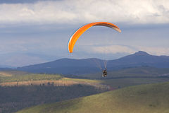 Paragliding over hilly valley Royalty Free Stock Images