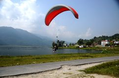 Paragliding over a lake Stock Photo