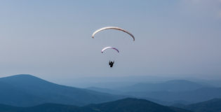 Paragliding over the mountain against blue sky Stock Image