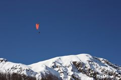 Paragliding over mountains. Scenic view of person paragliding in mid air above snowy mountains in blue sky Stock Photo
