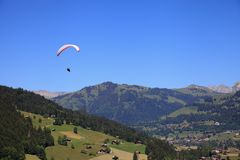Paragliding. Over the village of Gstaad, Switzerland Royalty Free Stock Photo