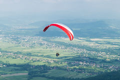 Paragliding over village Stock Photo