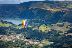 Paragliding in paradise landscape with volcano crater and lagoon in Azores. Paraglider above Lagoa das Furnas, Sao Miguel, Azores