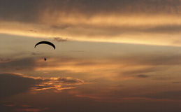 Paragliding pilots in the air. Sunset Stock Image