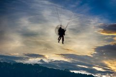 Paragliding, powered paraglider. And opportunity to admire sunset over land, but requires absence of thermals (anabatic wind) because of danger of collapse, air royalty free stock photo