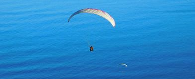 Paragliding from Signal Hill, Cape Town. A landscape view of para-gliders soaring above the sea at Mouille Point in Cape Town as seen from Signal Hill Stock Image