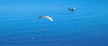 Paragliding from Signal Hill, Cape Town. A landscape view of para-gliders soaring above the sea at Mouille Point in Cape Town as seen from Signal Hill. Ocean Stock Photo