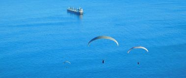 Paragliding from Signal Hill, Cape Town. A landscape view of para-gliders soaring above the sea at Mouille Point in Cape Town as seen from Signal Hill. Ocean Royalty Free Stock Photo