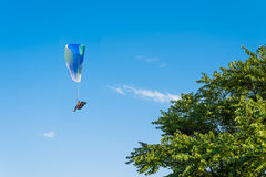 Paragliding in the sky. Man flying a paraglider on the sun Royalty Free Stock Photography