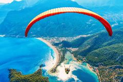 Paraglider tandem flying over sea with blue water and mountains Royalty Free Stock Image