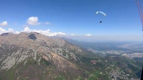 Paragliding sobre las montañas en un día de primavera hermoso, Italia