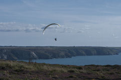 Paragliding at St Agnes. View from the St Agnes Peninsula in direction of St Ives with para glider small against the sky emphasising the sense of space and Stock Photos