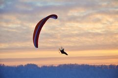 Paragliding at sunset. Man paragliding above the forest at sunset Royalty Free Stock Photo