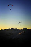Paragliding into the sunset. Two paragliders as silhouettes at sunset in the alps Royalty Free Stock Photo