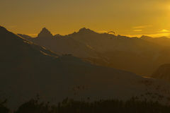 Paragliding into the sunset. A paraglider as a silhouette at a golden sunset in the alps Royalty Free Stock Photography