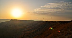 Paragliding sunset. Paragliding flying on sunset background Stock Photos