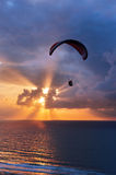 Paragliding at sunset on sea with sun beams Royalty Free Stock Photography