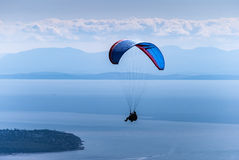 Paragliding in tandem with instructor over Grouse Mountain. Paragliding is a popular summer sport atop Grouse Mountain in Vancouver, British Columbia, Canada Royalty Free Stock Photos