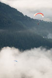 Paragliding top view. View from above, paragliding over the forest and clouds, two paragliders royalty free stock images