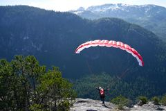 Paragliding. Woman with a red paraglider on the top of the mountain. Stock Image