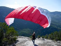 Paragliding. Woman with a red paraglider on the top of the mountain. Stock Photography