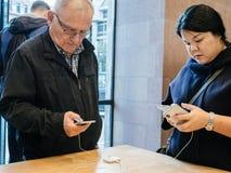 Paragone senior e teenager provando il nuovo iphone X Fotografia Stock Libera da Diritti