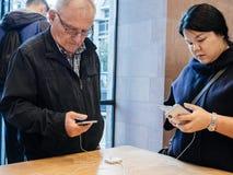 Paragone senior e teenager provando il nuovo iphone X Fotografie Stock