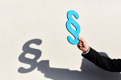 Paragraph as a symbol for pros and cons. Hand holds a paragraph as a symbol for pros and cons in the process Stock Photos