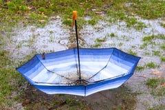 Paraguas al revés que flota en un charco que recoge la lluvia Foto de archivo