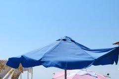 Paraguas azul en un día soleado de la playa Imagenes de archivo