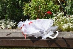 Paraguas blanco de la boda en un jardín verde entre las flores Imágenes de archivo libres de regalías