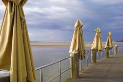 Paraguas cerrados del patio en terraza de madera del restaurante por la playa Imagenes de archivo
