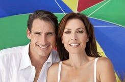 Paraguas colorido de los pares del hombre y de la mujer en la playa Foto de archivo libre de regalías
