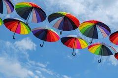 Paraguas coloridos con colores del arco iris en el cielo azul Imagen de archivo libre de regalías