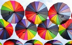 Paraguas coloridos con colores del arco iris en el cielo azul Imagenes de archivo