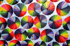 Paraguas coloridos con colores del arco iris en el cielo azul Imágenes de archivo libres de regalías
