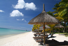Paraguas con las camas del sol en la playa tropical Fotografía de archivo