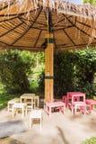Paraguas cubiertos con paja creativos con los posts de bambú en jardín Fotos de archivo