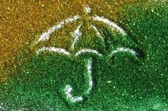 Paraguas de la chispa de oro y verde del brillo en el fondo blanco foto de archivo libre de regalías