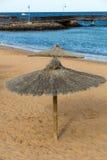 Paraguas de la paja en la playa Imagen de archivo libre de regalías