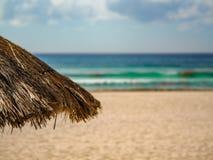 Paraguas de la paja en una playa azulverde del agua en Cancun, ingenio de México foto de archivo libre de regalías