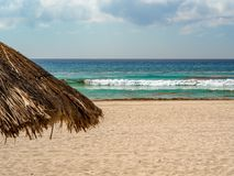 Paraguas de la paja en una playa azulverde del agua en Cancun, México imagen de archivo libre de regalías