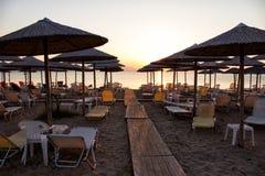 Paraguas de la silueta en la playa y la puesta del sol Foto de archivo