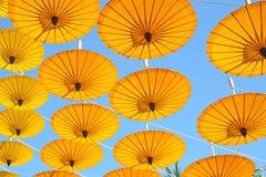 Paraguas de papel amarillo que flota en el cielo azul Fotografía de archivo