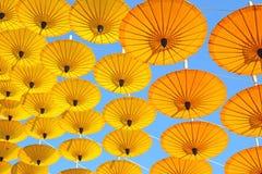 Paraguas de papel amarillo que flota en la textura del cielo azul Fotografía de archivo libre de regalías